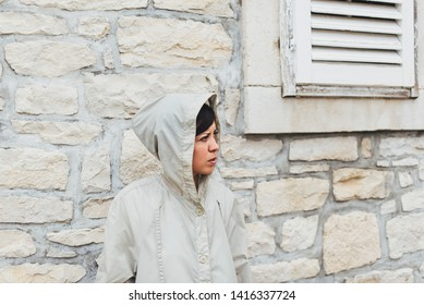 Girl in a raincoat in front of the stone wall