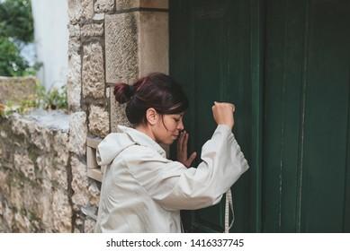 Girl in a raincoat knocking on green door