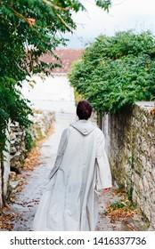Girl in a raincoat in a narrow street