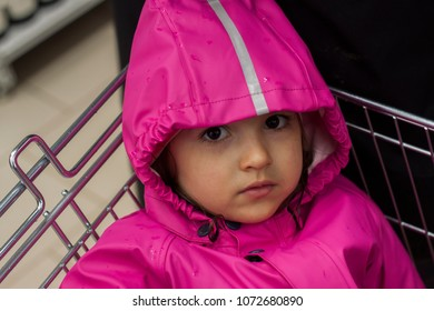 girl in a raincoat sitting in a shopping cart