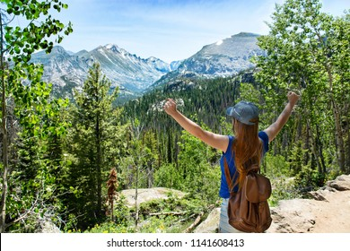Girl with raised hands relaxing on top of the mountain, looking at beautiful summer  landscape. View of Long Peak, Rocky Mountains National Park, Colorado, USA.
