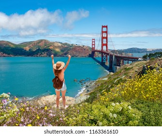Girl with raised hands relaxing on top of the mountain, enjoying beautiful view. Hiking trip. Golden Gate Bridge, over Pacific Ocean and San Francisco Bay, San Francisco, California, USA