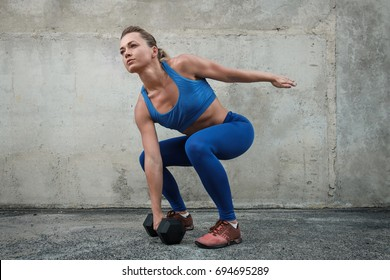 Girl raises a dumbbell in a training session near a concrete wall