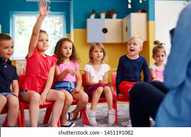 Girl raising her hand to ask question in classroom