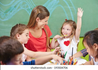 Girl raising her hand in preschool with painting a picture