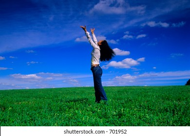 Girl reaches out to the sky on a grass field.