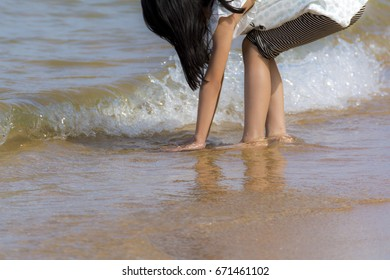 a girl reaching down and soaking hand in the sea