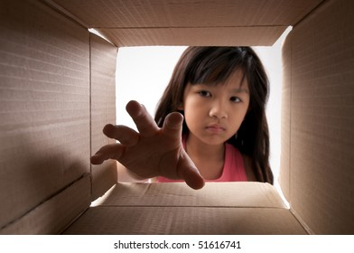 girl reaching for something inside the box