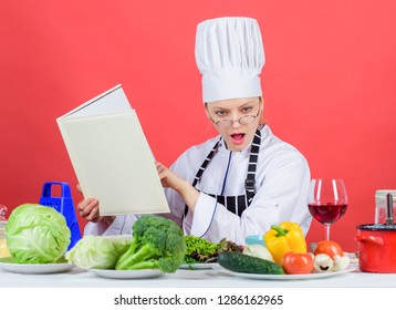 Girl read book best culinary recipes. Culinary education concept. Female in hat and apron knows everything about culinary arts. Improve cooking skill. Culinary expert. Woman chef cooking healthy food.