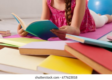 Girl reading among scattered books on the floor - closeup on hands