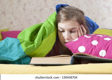 girl reading in bed under blanket