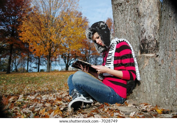 Girl reading the bible on a fall day