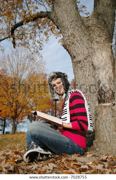 Girl reading the bible and smiling on a fall day
