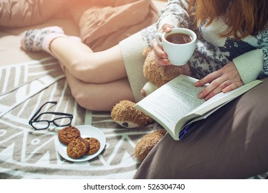 girl reading book in bed with a sweater and warm socks keeping your coffee in hand in the morning. the concept of new year mood.