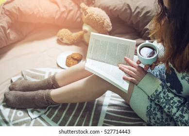 girl reading book in bed in a sweater and warm socks keeping your coffee in hand in the morning. the concept of new year mood.