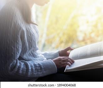 Girl is reading book beside window