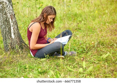 The girl is reading a book by the tree