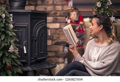 girl reading a book in a cozy home atmosphere near the fireplace, the concept of home rest
