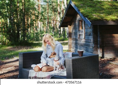 girl reading a book and dog sitting on the couch outdoors in the woods near the house