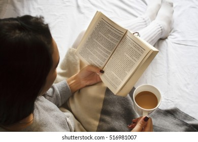 girl reading book and drinking coffee in bed in the morning