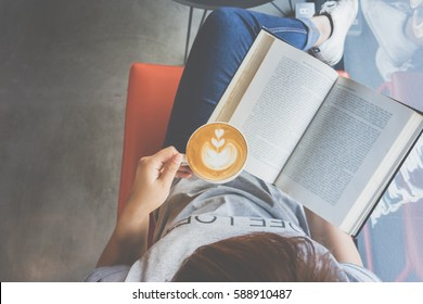 A girl reading book with drinking coffee latte with heart pattern on sofa in cafe