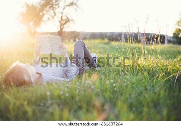 chica leyendo un libro en el césped en verano con luz de fondo de sol