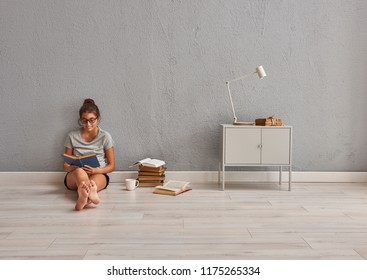 Girl is reading a book in the grey room.