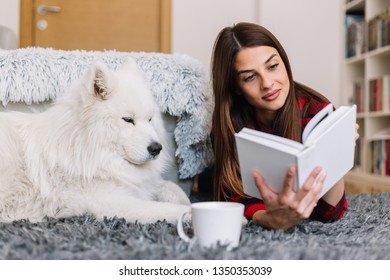 Girl reading a book with her dog beside her. Woman reads a book with dog on the floor.