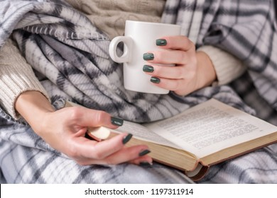 Girl reading book and holding cup of coffee and covered with retro blanket. Winter relaxation concept. Close up, selective focus