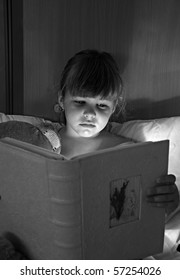 Girl reading a book with lamp