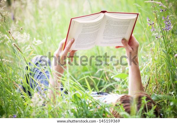a girl reading a book lying in meadow grass