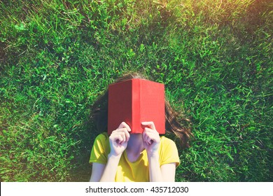 girl reading book lying in warm summer grass. view from above