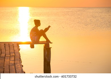 girl reading a book on a pier in the background of the sea and sunset. Ukrainian landscape