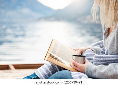 Girl is reading book on wooden pier by winter sea, mountains, beach. Cozy picnic with hot steamy beverages, tea, coffee or cocoa in thermos, warm plaid. Concept of enjoying life, relaxation.