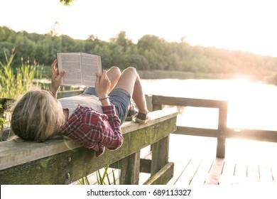 Mädchen, die draußen in der Sommersonne am See ein Buch lesen