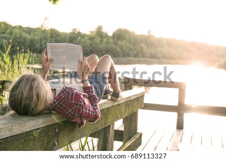 girl reading a book outside in summer sun at the lake