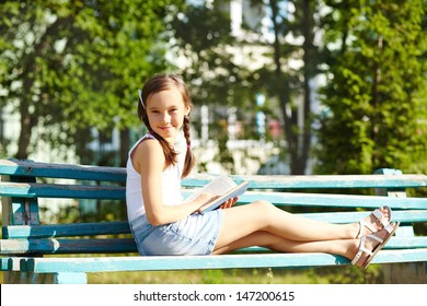 girl reading a book in the park sitting on the bench