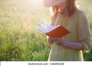 girl reading book at park in summer sunrise light