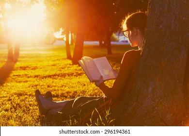 girl reading book at park in summer sunset light