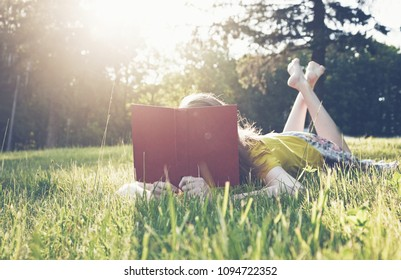 girl reading book in warm summer grass