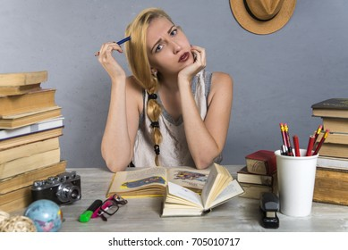 girl reading books sitting at a table among stacks of textbooks