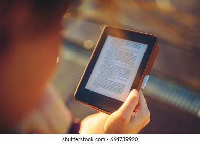 Girl reading e-book in sunny evening, selective focus