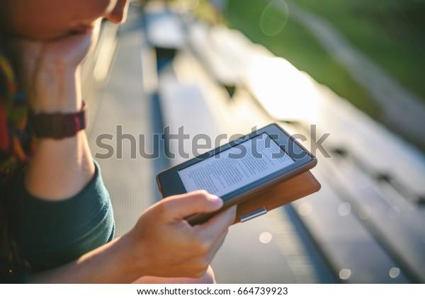 Девушка читает электронную книгу в солнечный вечер, селективный фокус