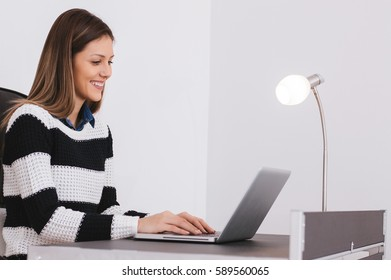 Girl reading good news on computer while working in home office