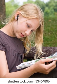 A Girl is reading a magazine while listening to music