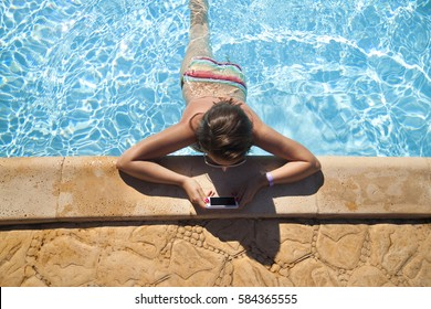 Girl reading messages at the pool