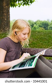 A girl, reading a newspaper while listening Musik