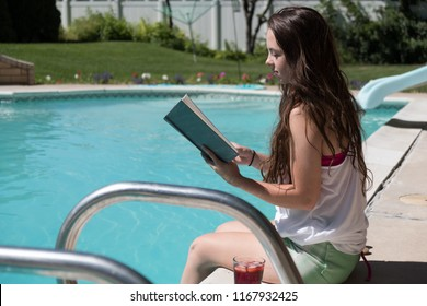 Girl reading a novel by the pool in shorts and tan top with a red punch and sandals at her side. Reading a book by an outdoor swimming pool in the sun in the backyard.