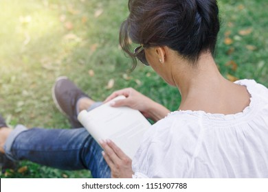 A girl is reading in the park. A concept of calm mood and relaxation in a park on the green grass. A middle-aged woman in blue jeans.