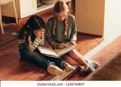 Girl reading storybook for her little sister. Two girls sitting on floor reading a book at home.